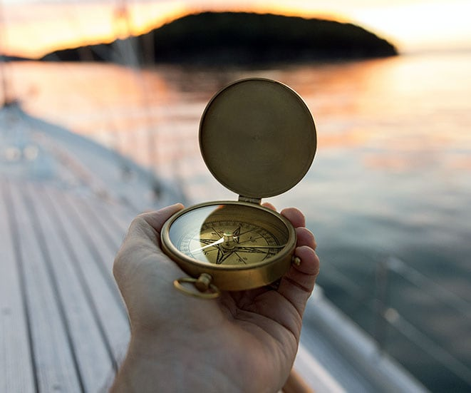 A hand holding a compass pointing out into the ocean.